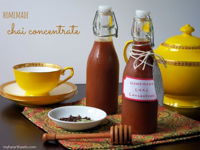 picture of homemade chai concentrate in glass bottles with yellow tea cups on a napkin